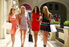 Fyra shoppa kvinnor som in går, shoppar Royaltyfri Foto