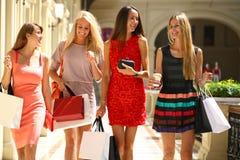 Fyra shoppa kvinnor som in går, shoppar Royaltyfri Fotografi