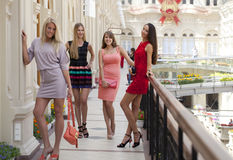 Fyra shoppa kvinnor som in går, shoppar Arkivfoton