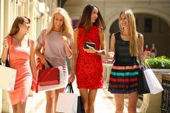 Fyra shoppa kvinnor som in går, shoppar Fotografering för Bildbyråer