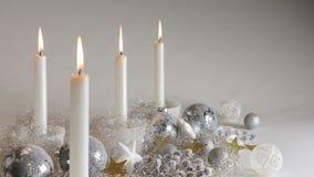Fyra silverlevande ljus i festlig garnering med blänker bollar och sparcling ängelhår stock video