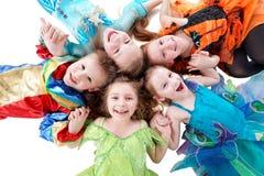 Fyra skratta flickor och en pojke, iklädd maskeradkläder, lie Royaltyfri Fotografi