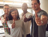 Fyra små och medelstora företagägare med tummar upp arkivfoto