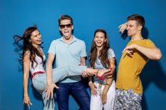 Fyra snygga vänner skrattar, medan stå framme av den blåa väggen som har säkra och lyckliga blickar arkivbilder
