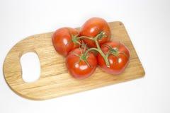 Fyra som är nya på de röda tomaterna för vinranka på den wood skärbrädan Arkivfoton