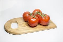 Fyra som är nya på de röda tomaterna för vinranka på den wood skärbrädan Royaltyfri Fotografi
