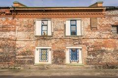 Fyra som är vita, och blåa fönster mot en vägg för röd tegelsten royaltyfria foton