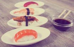 Fyra sorter Nigirisushi på ovala tefat Arkivfoton