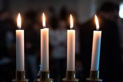 Fyra stearinljus i mörkt ställe royaltyfria bilder