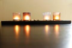 Fyra stearinljus på stenar royaltyfria bilder