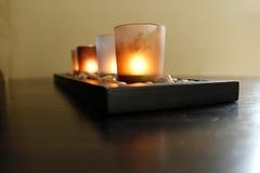 Fyra stearinljus på stenar Arkivbild