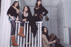 Fyra stilfulla modeller som poserar sammanträde på staketet Royaltyfri Foto