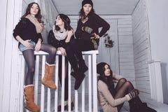 Fyra stilfulla modeller som poserar sammanträde på staketet Arkivbild