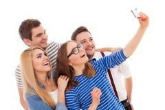 Fyra stilfulla ungdomarpå vit bakgrund Royaltyfri Foto