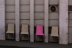 Fyra stolar och en är speciala Rosa unik stol fotografering för bildbyråer