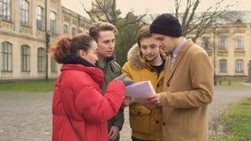Fyra studenter diskuterar föreläsningarna nära universitet lager videofilmer
