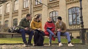 Fyra studenter sitter på bänken parkerar in arkivfilmer