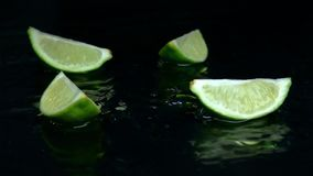 Fyra stycken av limefrukt faller på tabellen i vattnet Svart bakgrund långsam rörelse lager videofilmer