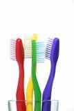 Fyra tandborstar i ett exponeringsglas Arkivfoton
