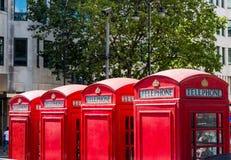 Fyra telefonaskar i London Arkivbild