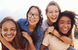 Fyra tonårs- flickor som har gyckel som utomhus piggybacking Arkivfoton