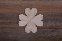Fyra trähjärtor i formen av en växt av släktet Trifolium för fyra blad på en woode Arkivbild