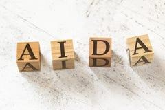 Fyra träkuber med bokstavsAIDA som betyder uppmärksamhetmedvetenhetintresse Desire Action på det vita funktionsdugliga brädet arkivfoto