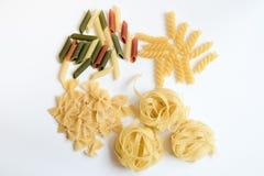 Fyra typer av pasta på vit Fotografering för Bildbyråer