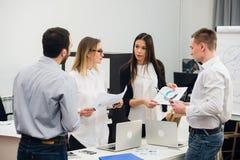 Fyra unga affärspersoner som arbetar som ett lag, samlade runt om bärbar datordatoren i ett modernt kontor för öppet plan Royaltyfri Bild