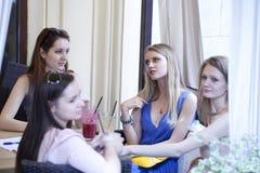 Fyra unga flickor har en vila i ett sommarkafé Royaltyfria Foton