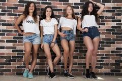 Fyra unga flickor i vita t-skjortor och jeanskortslutningar som står nea royaltyfri foto