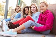 Fyra unga flickor som ut hänger i, parkerar tillsammans Royaltyfria Foton