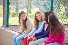 Fyra unga flickor som ut hänger i, parkerar tillsammans Royaltyfri Bild