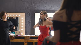 Fyra unga härliga kvinnor som poserar makeupspegeln och, korrigerar klänningen och smink stock video