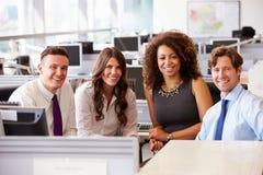 Fyra unga kontorskollegor som ser till kameran royaltyfri foto
