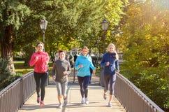 Fyra unga kvinnor som joggar över bron fotografering för bildbyråer