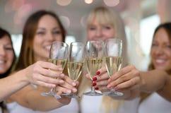 Fyra unga kvinnor som rostar med champagne Arkivfoto