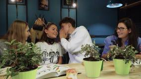 Fyra unga studenter sitter på ett avbrott mellan grupper i ett kafé, att skratta, skoja och äta mellanmål för att dricka kaffe stock video