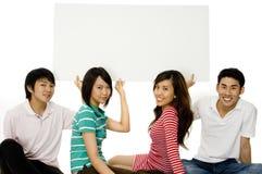 Fyra unga vuxen människa med tecknet Royaltyfria Foton