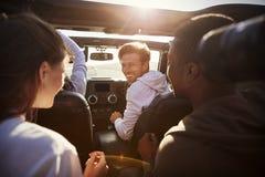Fyra unga vuxna vänner tillsammans i en bil på en vägtur royaltyfri fotografi