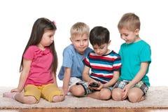 Fyra ungar med en ny grej royaltyfria foton