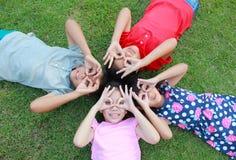 Fyra ungar som har gyckel i parkera Arkivbild