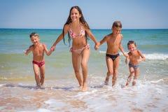 Fyra ungar som kör från havet på stranden Fotografering för Bildbyråer