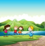 Fyra ungar som spelar med ett rep nära floden Royaltyfria Bilder