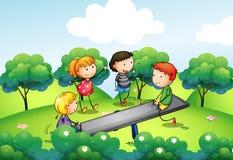 Fyra ungar som spelar med gungbrädet på kullen Fotografering för Bildbyråer