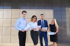 Fyra ungdomar, två män och två kvinnor, studenter, meddelar, Royaltyfri Bild