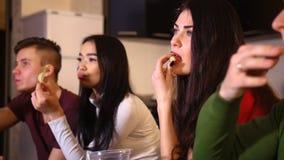 Fyra ungdomarsom sitter på soffan och den hållande ögonen på fotbollsmatchen äta matskräp arkivfoto