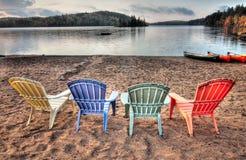 Fyra uteplatsstolar som ser över laken fotografering för bildbyråer