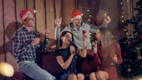 Fyra vänner sjunger och dricker champagnevin på jultid stock video