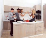Fyra vänner som förbereder matställen royaltyfri bild
